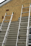 Two Ladders. Against the exterior of a partially sided house Stock Photo