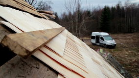 Two ladders attached to the cedar wooden shingle shake roof and white minivan stock video footage