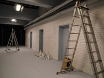 Two ladders in a studio. With brick walls and neon lights in the ceiling royalty free stock images