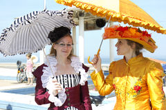 Two ladies. SOULAC SUR MER, FRANCE - JUNE 5, 2011:portrait of two ladies with umbrella at the Soulac 1900 festival on june 5, in Soulac sur mer, France. Every royalty free stock image