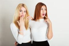Two ladies in awkward moment. Friends goals concept. Two ladies in awkward moment. Blonde girl together with mulatto lady, Standing next to each other Stock Photography