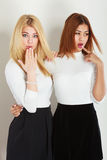 Two ladies in awkward moment. Friends goals concept. Two ladies in awkward moment. Blonde girl together with mulatto lady, Standing next to each other Royalty Free Stock Image