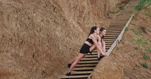 Two ladies in a black sportswear stretching legs on the wooden stents beside the beach background big rocks.  stock video footage