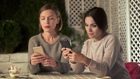 Two ladies chatting on phones instead live communication, gadget addiction. Stock photo stock image