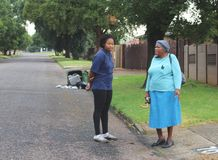 Two ladies chatting in a street of Alberton, South Africa stock image