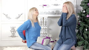 Two ladies exchanging Christmas presents. Two young, blond hair, women woman, lady, ladies exchanging giving each other Christmas presents, gifts. Smiling, being stock video