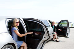 Two ladies exiting limousine Royalty Free Stock Photos