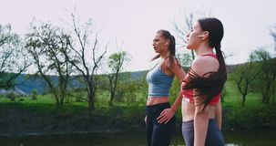 Two ladies with a fit bodies closeup running together in amazing landscape view wearing wireless airpods they enjoying