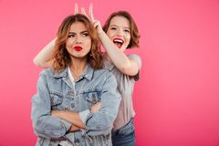 Two ladies friends standing isolated have fun. Royalty Free Stock Photos