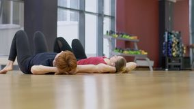 Two ladies are having a yoga class in modern gym, slow motion. Women are doing upforward bow pose on elbows near the big window and turning into other position stock video