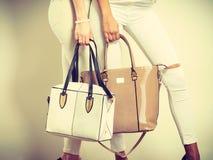 Two ladies holding handbags. Stock Photo