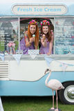 Two ladies holding ice cream in van with flamingo. Two ginger haired ladies holding ice cream in van with flamingo on grass. Portrait photo with blank text space stock image