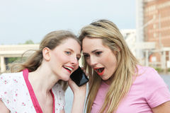 Two ladies listening to a mobile phone. Two ladies standing with their heads close together listening to a conversation over a mobile phone, with one women Royalty Free Stock Image