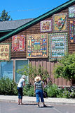 Two Ladies Looking At Quilts. Two ladies enjoy looking at quilts hung on a building at the 2011 outdoor quilt show in Sisters, Oregon Stock Images