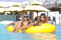 Two ladies lying on inflatable ring Stock Images