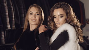 Two ladies posing in rich fur coats in boutique for advertising. Slowly.  stock footage