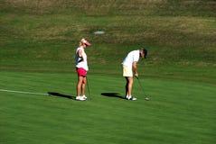 Two ladies on the putting green, Marbella, Spain. Two women playing golf on the putting green at the Rio Real Golf Club, Marbella, Costa del Sol, Malaga royalty free stock photos