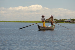 Two ladies rowing standing up Tonle Sap Lake Cambodia Stock Photography