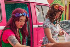 Young ladies selling Candy at a festival royalty free stock image
