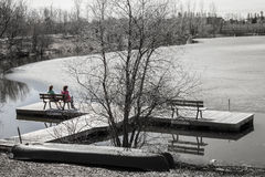 Two Ladies Sitting On A Bench Looking At The Thawing Lake. Stock Image