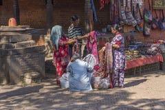 Two ladies unidentified negotiate the price of clothing. KATHMANDU, NEPAL - DECEMBER 02, 2013: two ladies unidentified negotiate the price of clothing in a stall Stock Photos