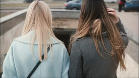 Two ladies walk down to a pedestrian tunnel. Gilfriends in stylish clothes come up to subway. Friends walking together. Two ladies walk down to a pedestrian stock video footage