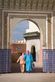 Two ladies walk into a mosk. Two ladies are walking through a gate to into a mosk Royalty Free Stock Images