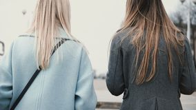 Two ladies walk up from a pedestrian tunnel. Back view close up blonde and brunette females in stylish clothes chatting. Two ladies walk up from a pedestrian stock footage