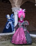 Two ladies wearing brightly colored blue and pink masks and costumes at Venice Carnival. Stock Images