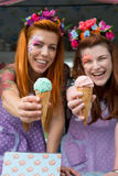 Two ladies wearing flower headbands holding ice cream from truck royalty free stock image