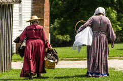 Two ladies / women walking home in colonial dress. Royalty Free Stock Photo