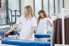 Two ladies working in dry cleaners. Two ladies working in a dry cleaners royalty free stock photography