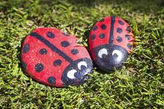 Two ladybugs on grass. Two little homemade stone colorful ladybirds sitting on grass Royalty Free Stock Photography