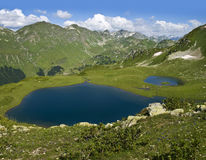 Two lakes in the mountains with grass and flowers Royalty Free Stock Images
