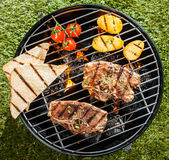 Two lamb chops cooking on a BBQ. On a portable grill with tomato, potatoes and slices of toast on a sunny summer day outdoors on the grass, overhead view Royalty Free Stock Image