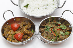 Two lamb curries with rice. A bowl of spiced lamb curry with coriander leaves and slivers of red and green chillies, next to a bowl of Lahore-style lamb curry royalty free stock images