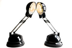 Two lamps. Two ignited black lamps on white bottom Stock Images