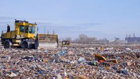 Two landfill compactors move across a landfill side. Two landfill compactors drive through a large garbage site stock video footage