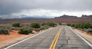 Two Lane Highway Rock Buttes Utah Wilderness United States. Rain clouds come over the mountains in the Utah desert Stock Images