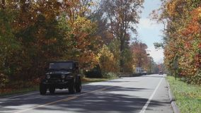 A two-lane road in Autumn (1 of 2). A view or scene from around town stock video
