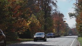 A two-lane road in Autumn (2 of 2). A view or scene from around town stock video