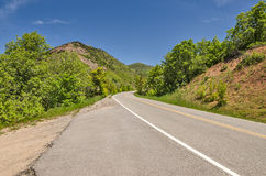 Two Lane Road in the Mountains. Two-lane road with a big curve as it winds through mountains with vibrant green trees and blue skies royalty free stock photography