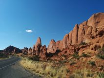 Road next to rounded rock formations in Arches National Park. Two-lane road next to rounded rock formations and grass in Arches National Park Royalty Free Stock Photo