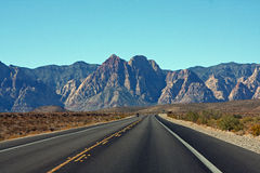 Two-lane road to Red Rock Canyon. Two-lane road through Red Rock Canyon in the outskirts of Las Vegas, Nevada.  Red Rock Canyon is a scenic national Royalty Free Stock Images