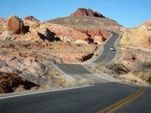 Two-lane road weaving through desert. Valley of Fire in Nevada. Two-lane road weaving through desert landscape Royalty Free Stock Photo