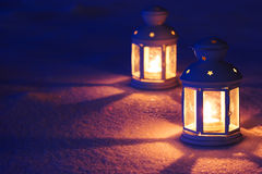 Two Lantern with burning candle on snow in the evening. Tinted p Stock Photo