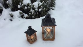 Two lanterns under the snow with pines in background. Two lanterns with candles under the snowfall with pines in background stock footage