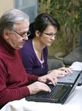 Two laptops. A woman and her senior father typing on two laptops at home royalty free stock photos