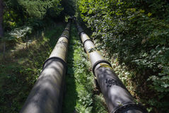 Two large black water pipes, converging in distance. Royalty Free Stock Photography