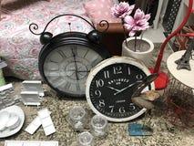 Two clocks, some flowers and a bird sculpture. Two large black and white clocks, some flowers and a bird sculpture Stock Photos